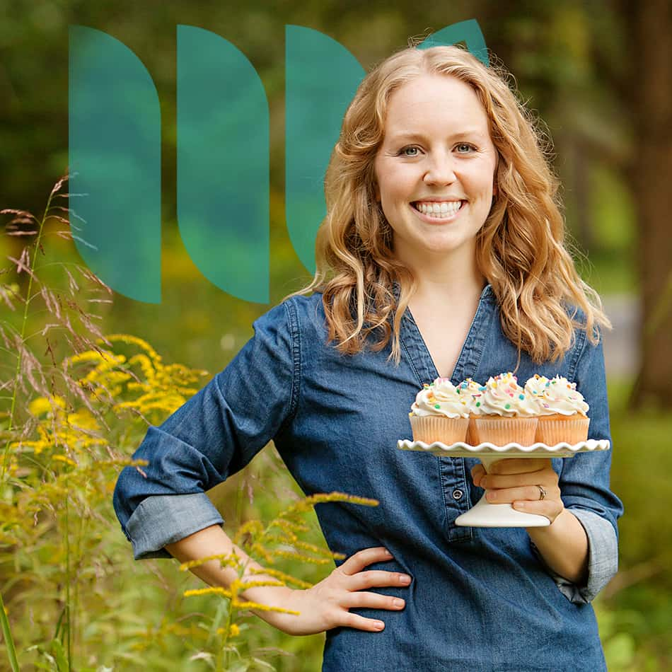 Beth from The First Year Blog smiles at the camera. She is holding a cake stand piled with cupcakes.