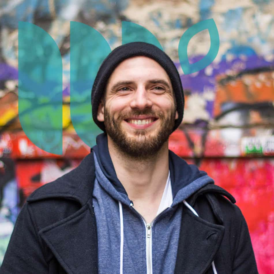 A Caucasian man in a beanie hat is smiling, looking off into the distance. He is standing in front of a graffiti'd wall.