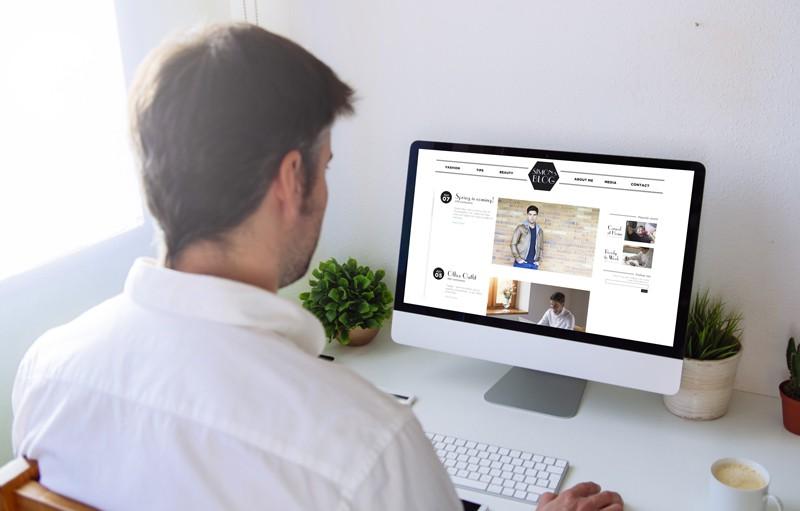 A man blogging on a desktop computer.