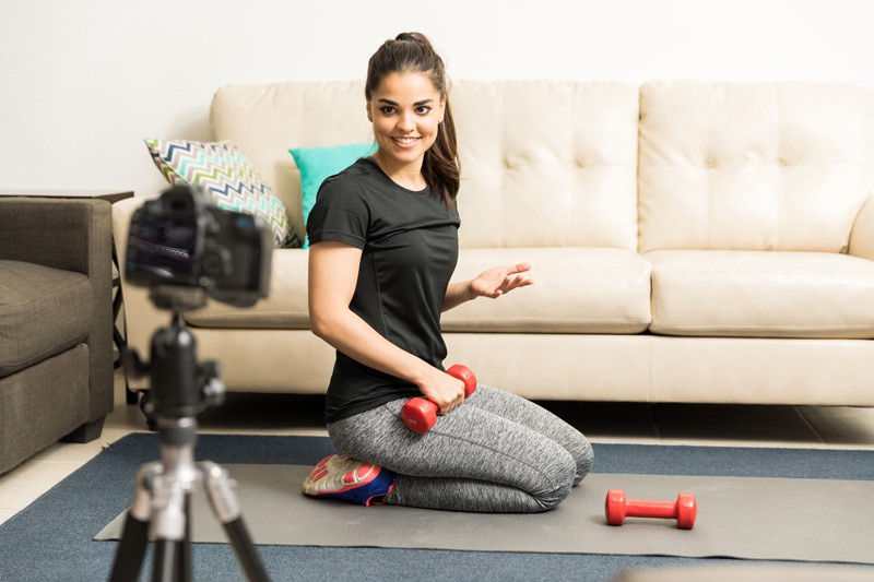 A woman vlogging for a fitness channel, kneeling on a yoga mat with small hand weights.