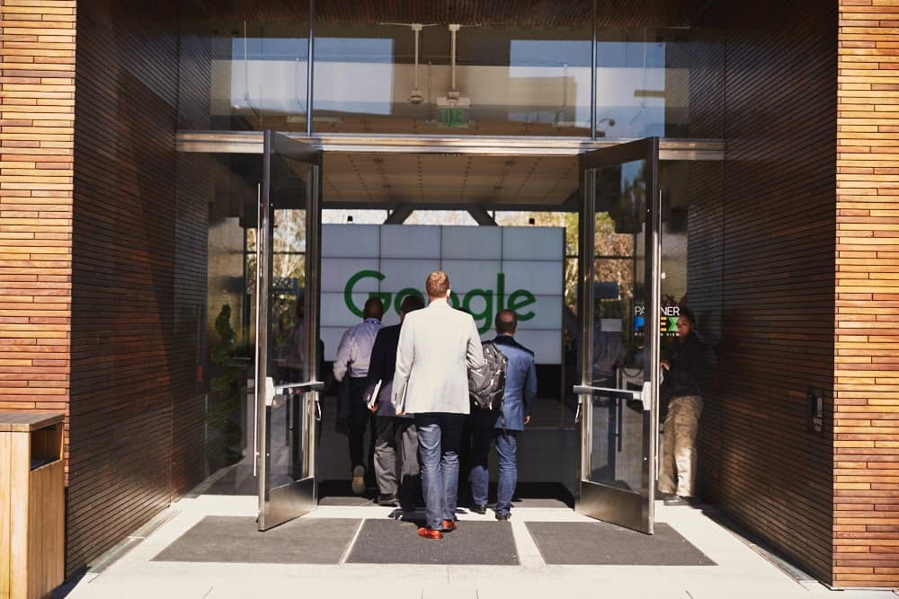 A group of men in suits entering a Google building.