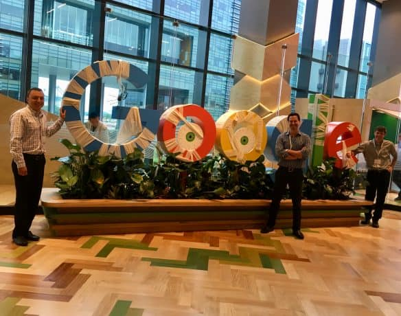 Brad Hagman (left), Eric Hochberger (center) and Steve Marsi (right) by a Halloween-decorated Google sign at Google's Singapore offices.