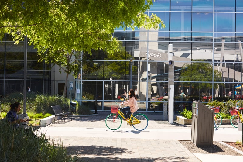 A woman rides a Google bike on the Google campus in Mountain View, CA.