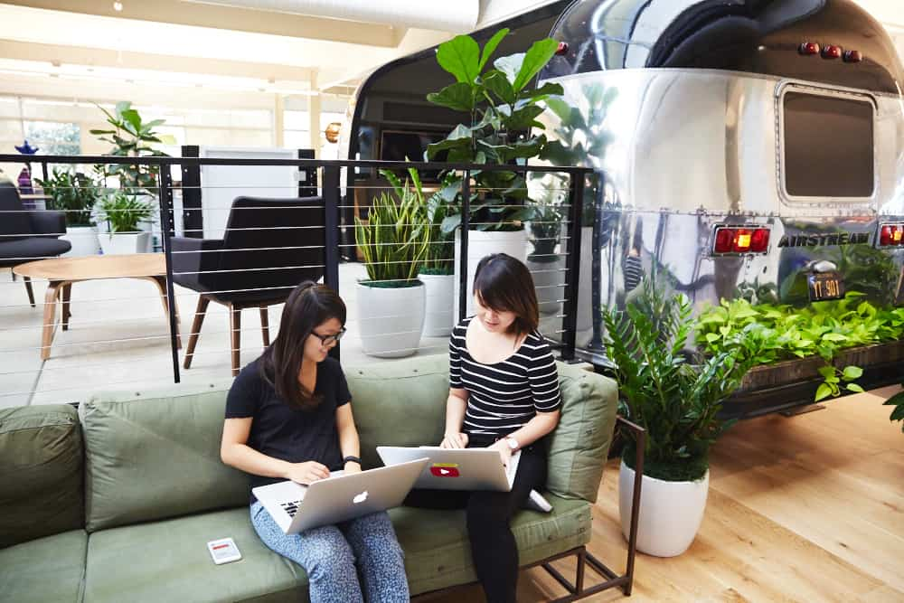 Two female bloggers work on laptops in a coworking space.