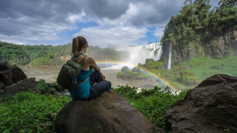 Kristin Addis sits in front of a waterfall, complete with rainbow arcing in front of her.