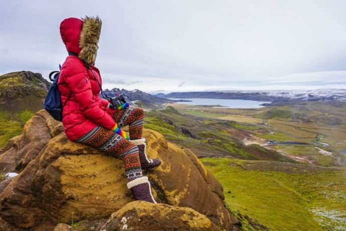Kristin Addis looks out over a low prairie, wearing a parka and warm boots.