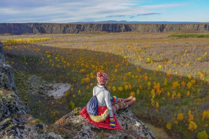 Kristin Addis sits atop a rocky outcrop overlooking a field of flowers.