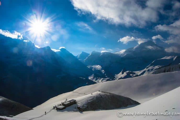 The sun shines over a snowy mountain range.
