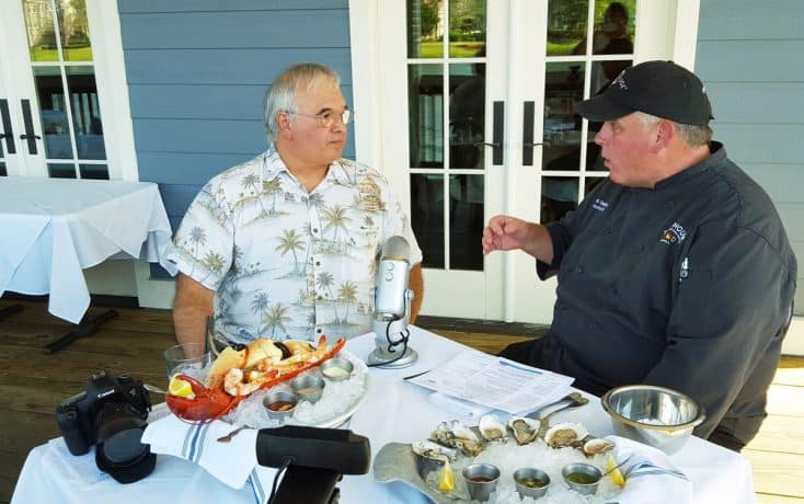 Chef Dennis recording an interview. On the table between them are various seafood dishes.
