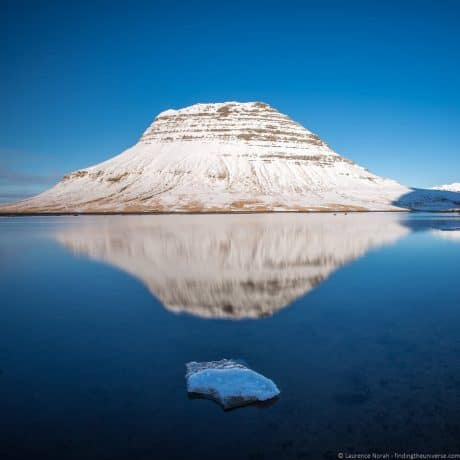 Kirkjufell in Iceland, with reflection in the icy lake at its base.