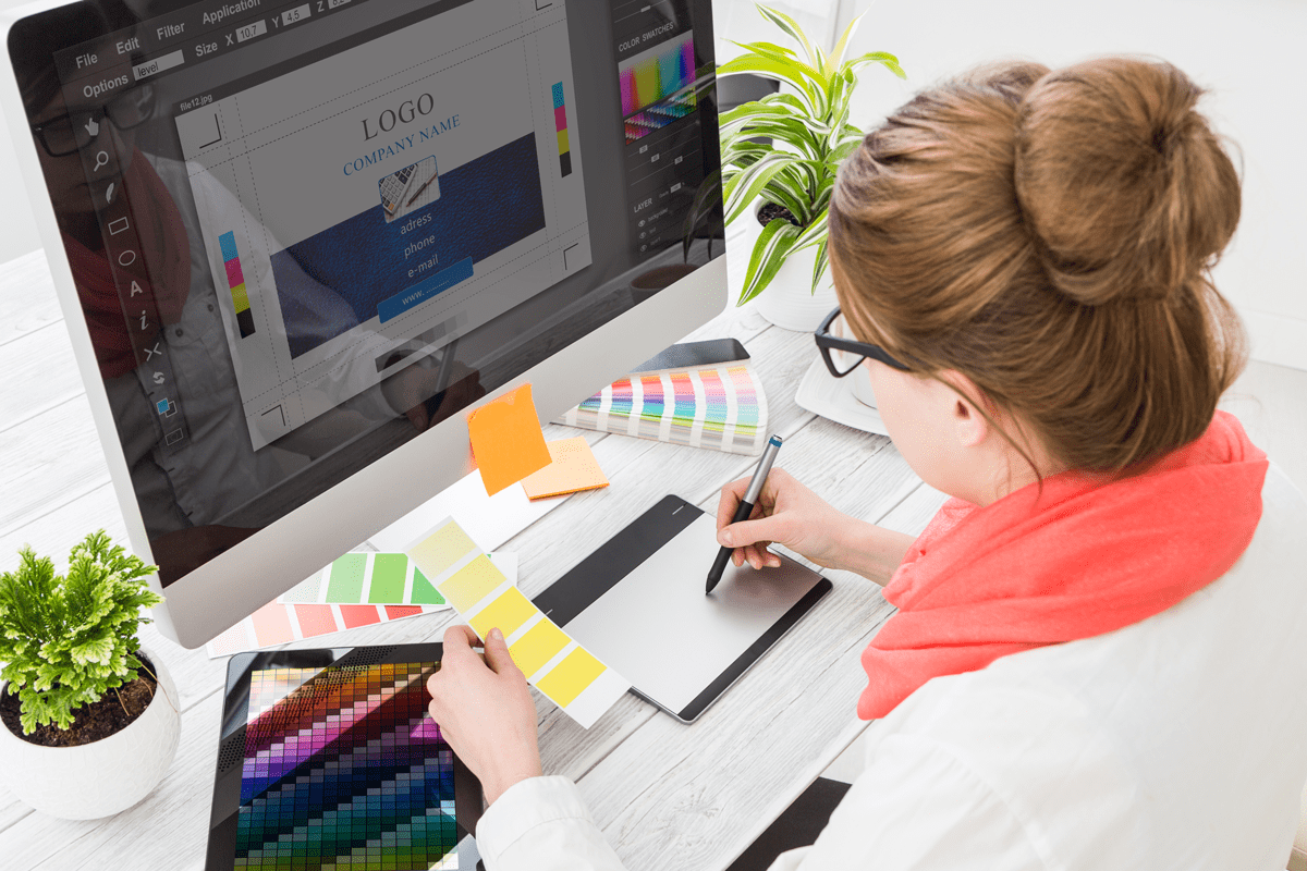 A woman compares color swatches while designing promotional materials.