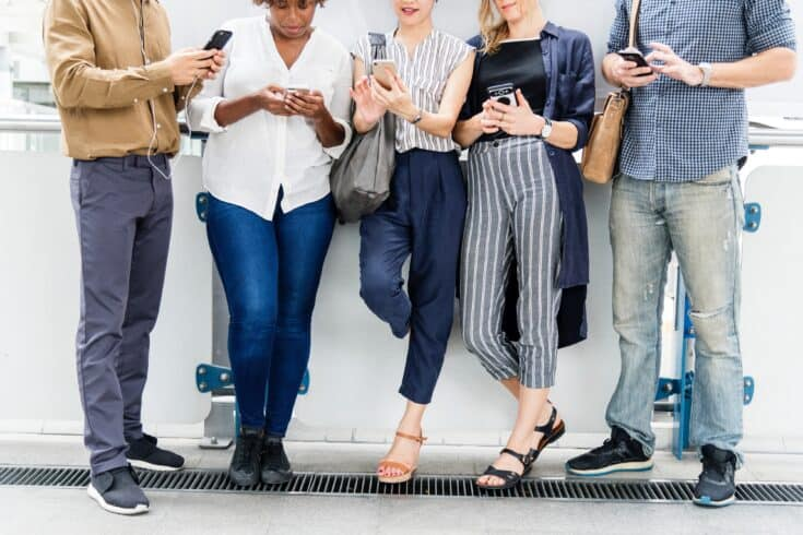 group of people standing against a wall looking at their smartphones