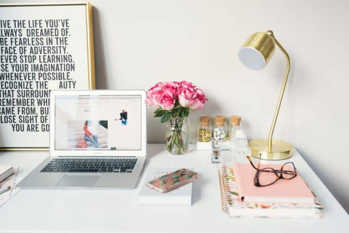 A desktop with a laptop computer, smart phone, bouquet of flowers, lamp, notebooks and a pair of glasses on the surface.