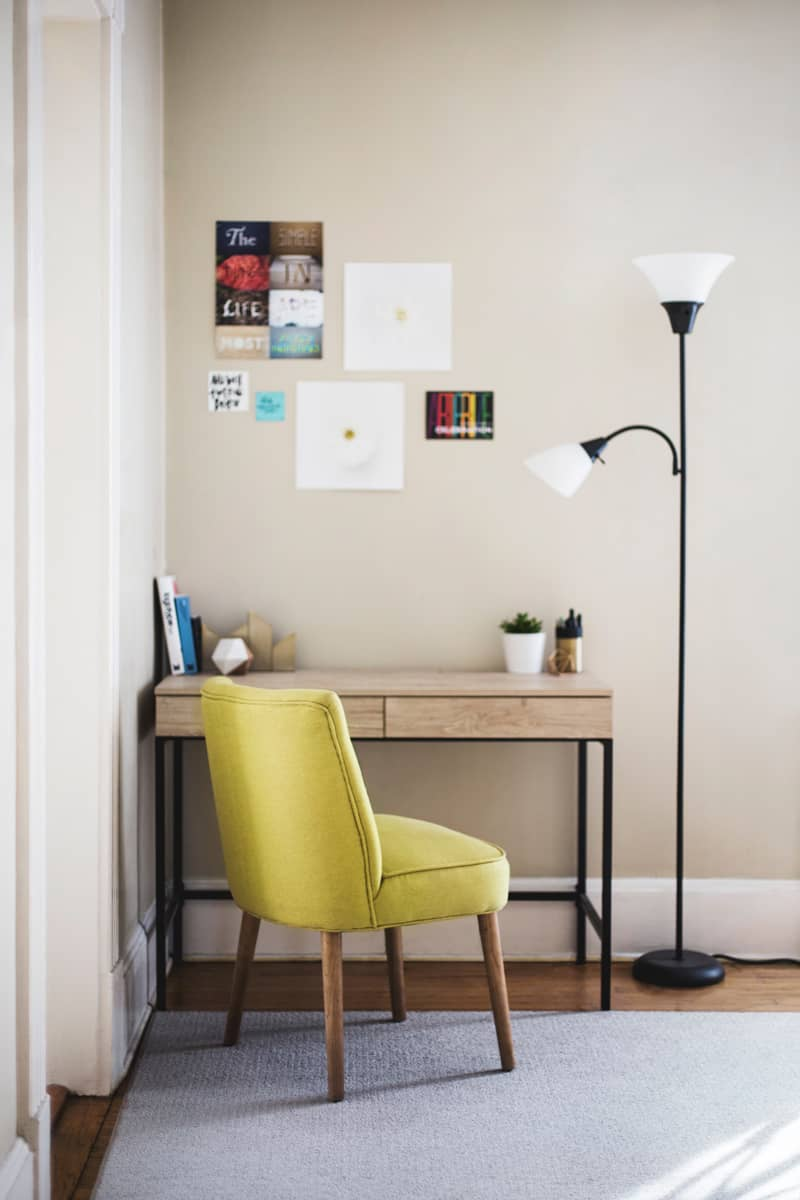 A desk sits in the corner of a light with plenty of natural light. A green upholstered chair sits in front of it.