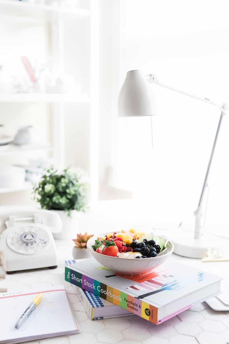 A desk with a lamp, stack of books topped with a bowl of fruit, phone, plant, and planner with pen.