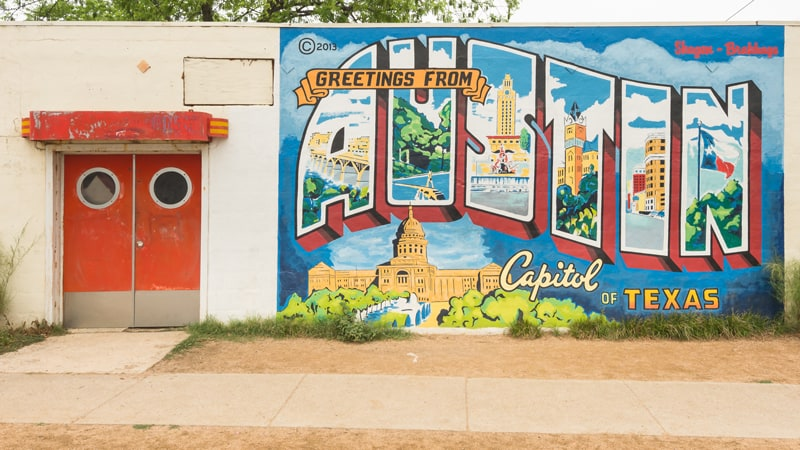 "A mural depicting the word ""Austin"". The letters are filled with various landmarks from Austin, TX, and the capitol building beneath it."