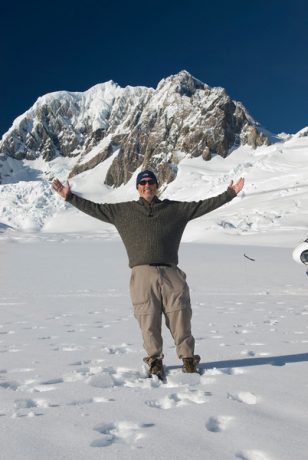 Gary stands atop a snow-covered mountain peak.