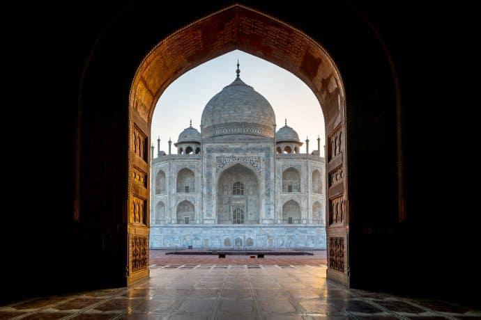 The Taj Mahal seen through an archway entrance.