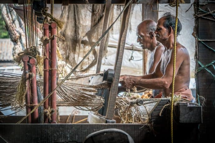 Men at work in India processing coir (used to make doormats and rope),