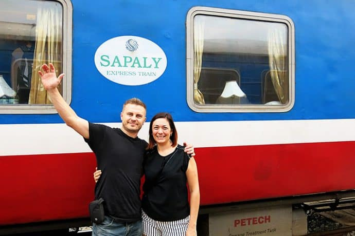 Andrzej Ejmont of Wanderlust Storytellers stands in front of a Sapaly Express Train.