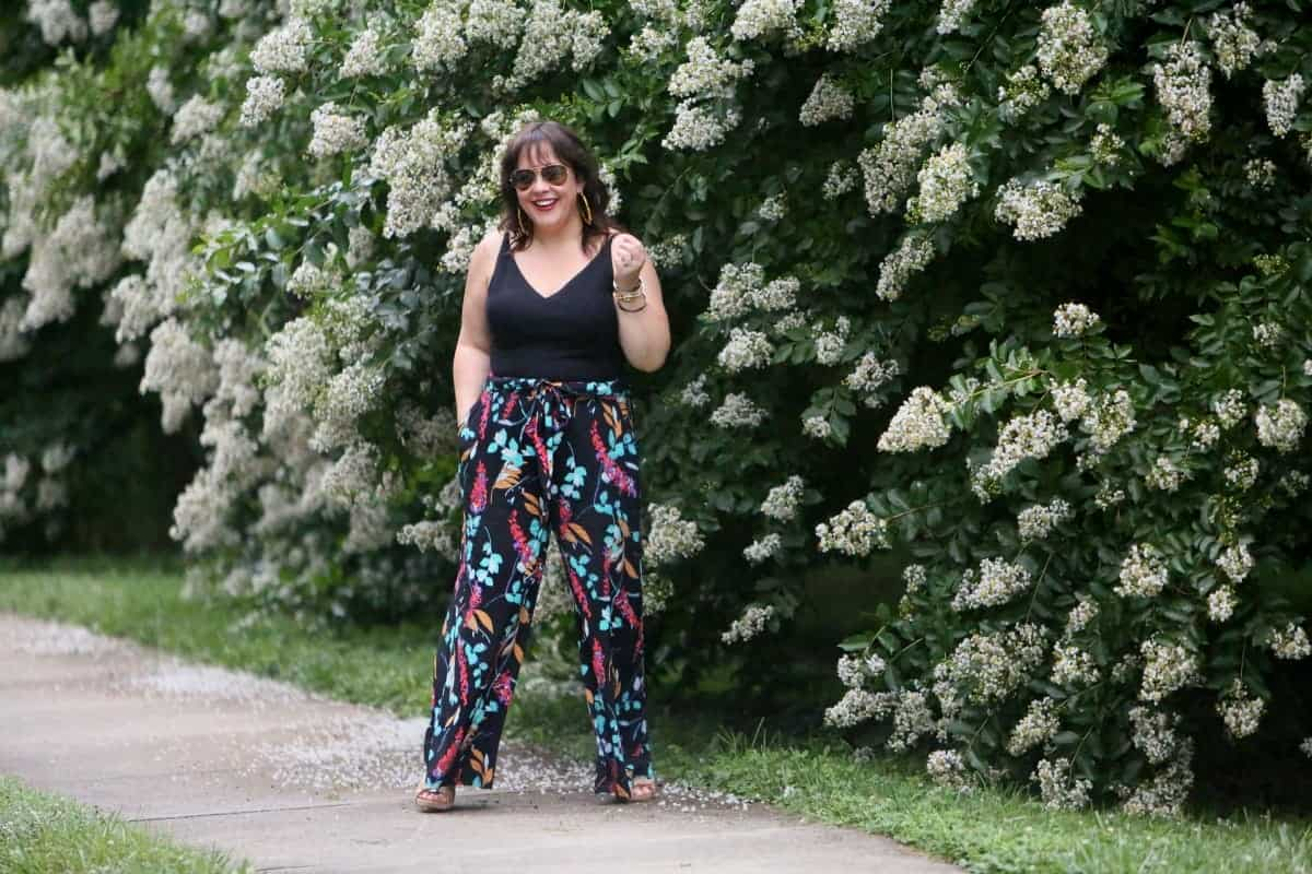 Alison Gary from Wardrobe Oxygen standing in front of flowery bushes