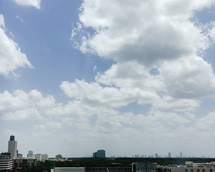 The Houston, Texas city skyline, beneath partly cloudy blue skies.