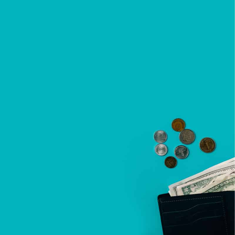 An open wallet spilling onto a teal background.
