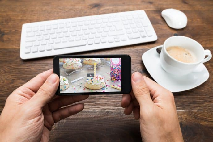 A smart phone plays a video ad; in the background is a tabletop with wireless keyboard and mouse, and a cup of coffee.