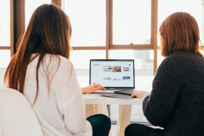 Two women surf the web on a laptop computer.