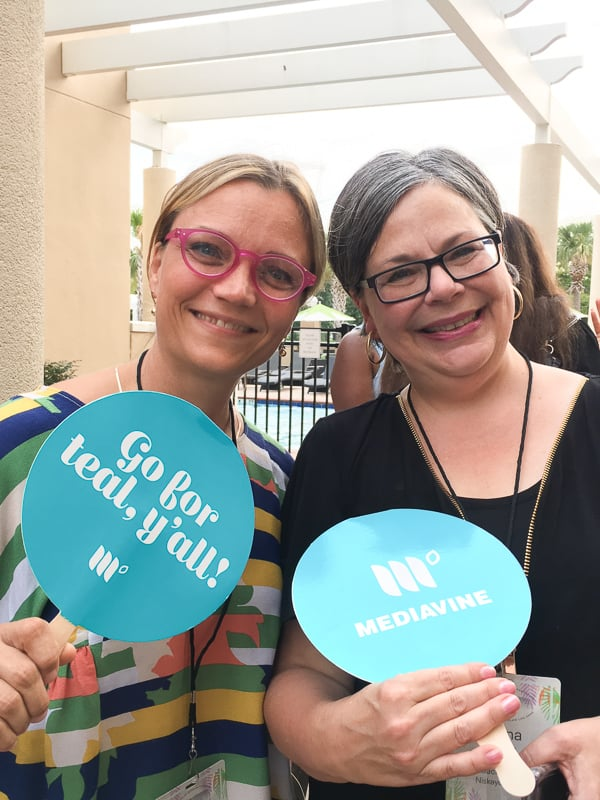 "Haven attendees holding Mediavine-branded hand fans reading ""Go for teal, y'all!""."