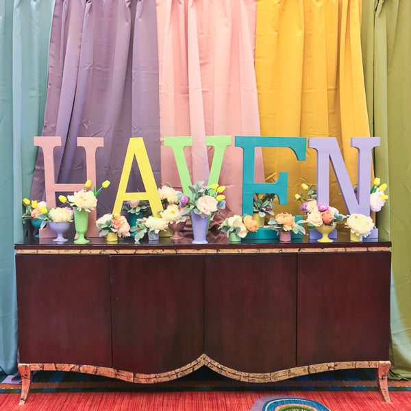 "A Haven photo booth, showing a rainbow of colored curtains in the background, and a table top decorated with colorful vases and multi-colored wooden letters reading ""Haven""."