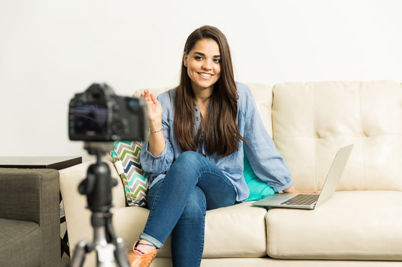 A woman sits on a white couch with a laptop beside her, vlogging.
