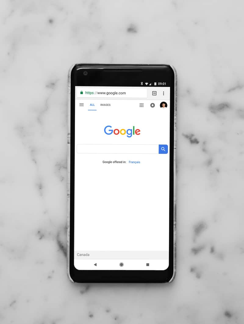 A mobile phone opened to the Google search bar home page.