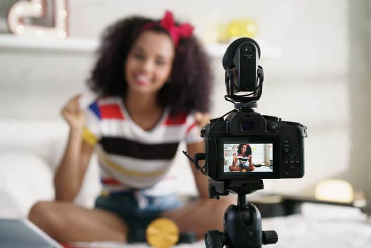 woman filming herself with a camera set up on a tripod
