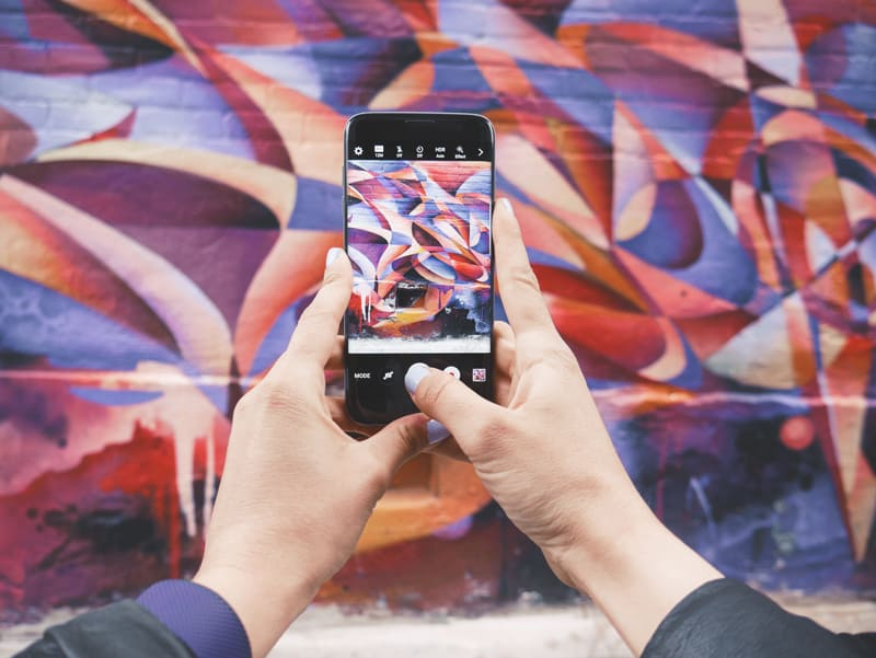 A mobile phone user taking a photograph of a mural.