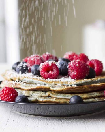 Pancakes with berries and powdered sugar.
