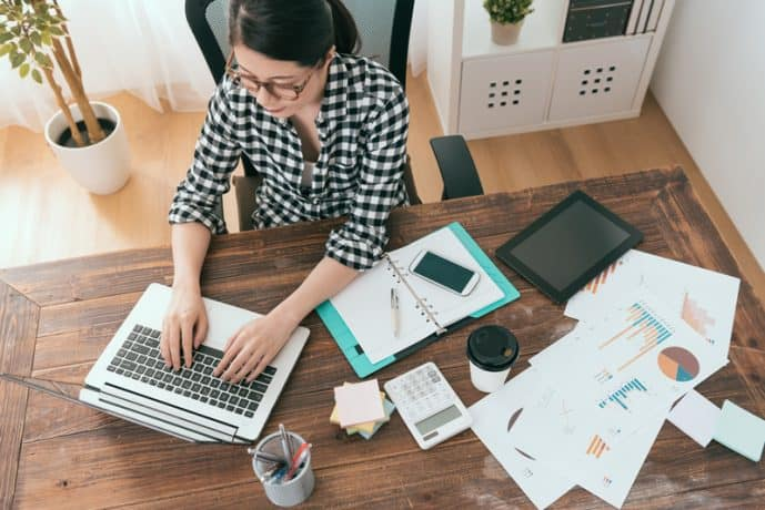 top view of woman typing on laptop with office supplies scattered on table