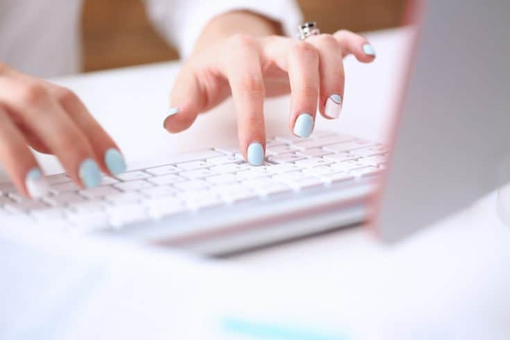 woman's hands with blue and white nails typing on a keyboard