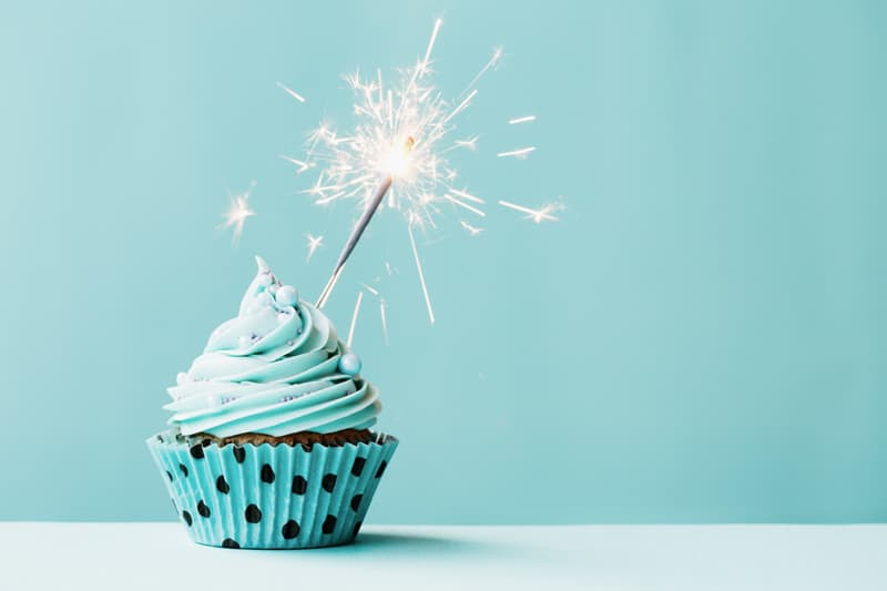 A teal cupcake with a sparkler candle.