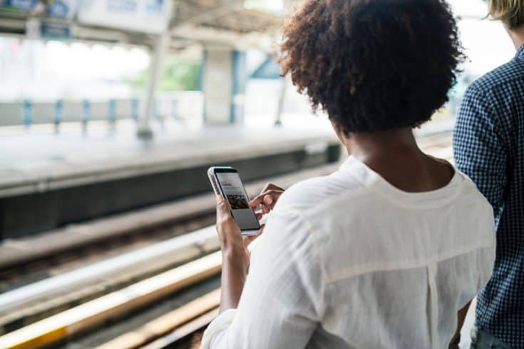 A woman standing in a train station browses the Internet on a smart phone.