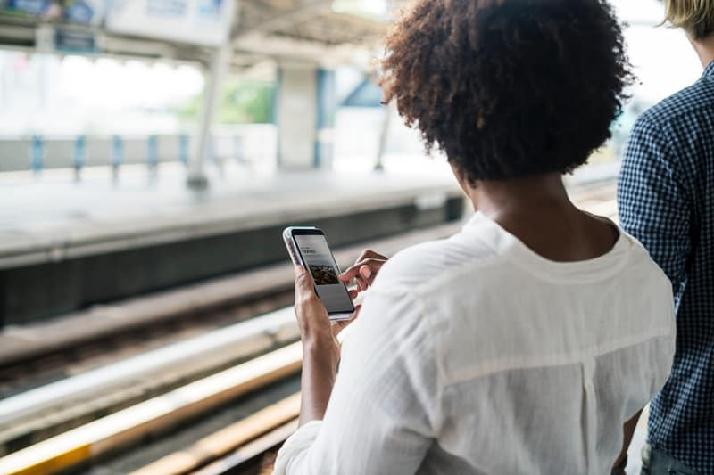 A woman using a smart phone in front of train tracks.