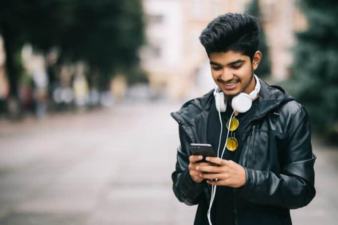 man using phone walking on street