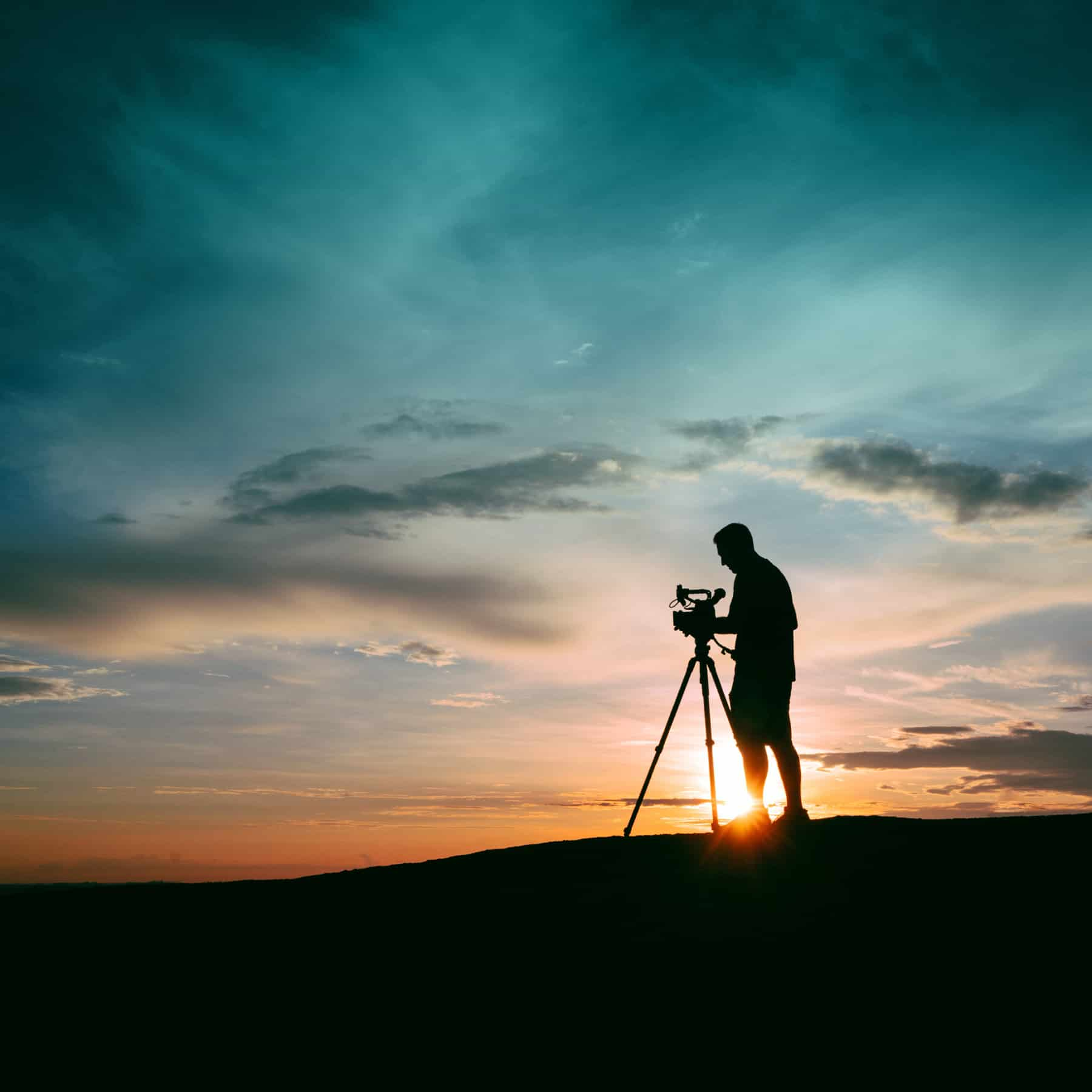 A man in silhouette setting up a camera, with the sun setting behind him.