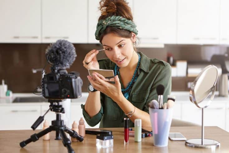 beauty blogger filming herself putting on makeup in a mirror
