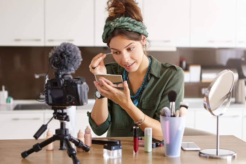 woman doing make-up in front of a camera