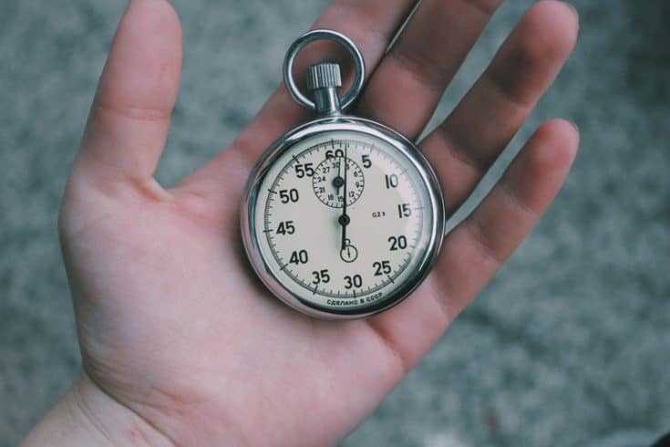 A hand holding a pocket watch.