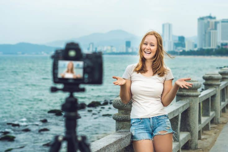 A woman filming a vlog in front of a pier.