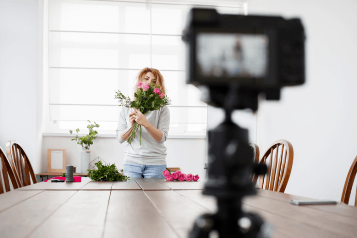 A camera records a woman holding a bouquet of flowers across a kitchen table.