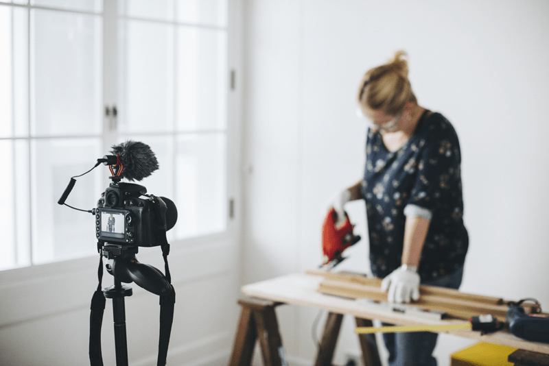 A camera films a woman working on a DIY carpentry project.