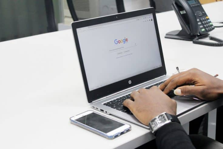 Hands typing at a laptop computer on the Google search homepage.